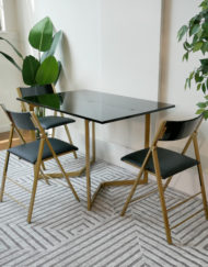 Flip-console-table-glossy-black-with-gold-legs-and-black-nano-chairs-in-grey-room