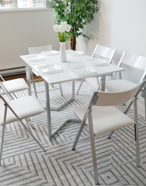 Flip-console-table-in-glossy-white-opened-in-dining-form-with-six-nano-chairs-in-a-modern-room-with-grey-carpet