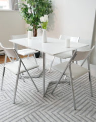 Flip-console-to-dining-table-in-glossy-white-opened-in-dining-form-with-4-nano-chairs-in-a-modern-room-with-grey-carpet